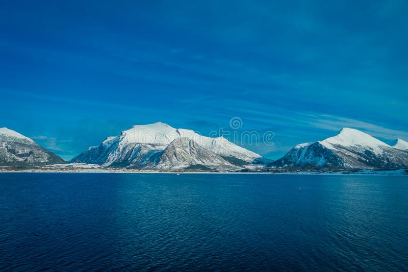 Outdoor view of beautiful mountain partial covered with snow, the in Hurtigruten region in Norway. Outdoor view of mountain range in Norway. The beautiful stock photography