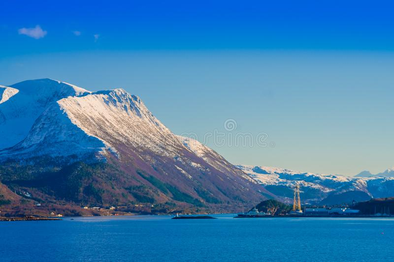 Outdoor view of mountain range in Norway. The beautiful mountain partial covered with snow in Hurtigruten region with. Some buildings in the horizont in Norway royalty free stock image