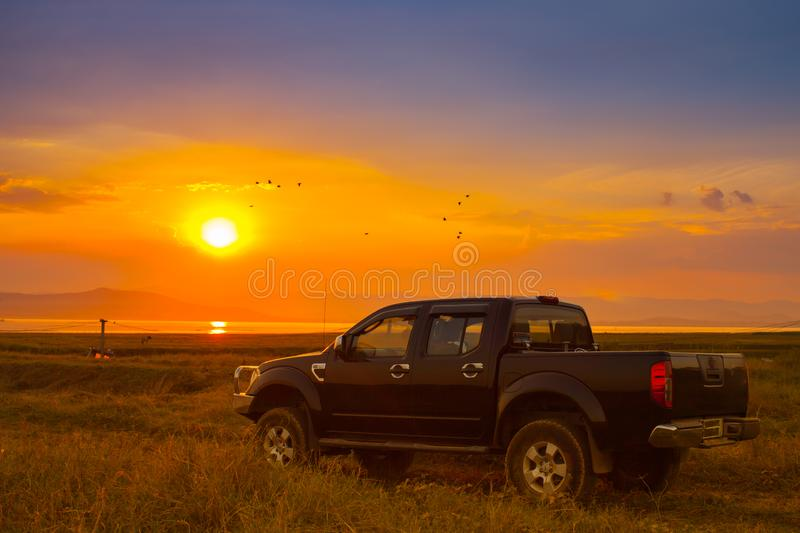 Outdoor view of pick-up truck with sunset background. Under cloudy sky stock images