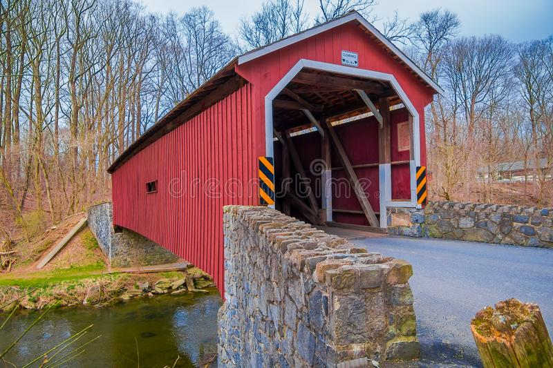 Outdoor view of red covered bridge inside of the forest over a small river in Lancaster stock photos