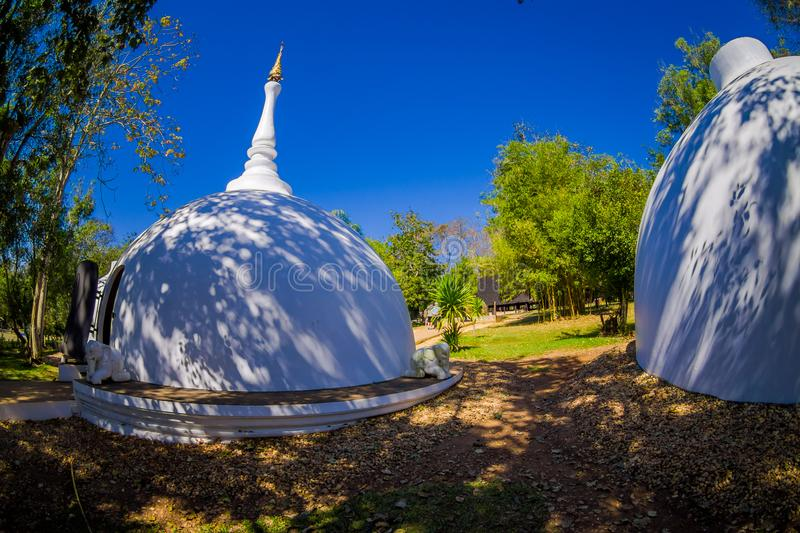 Outdoor view of white building in form of dome in Baan Dam or Black House, Museum of Art in Chiang Rai, Thailand royalty free stock photo