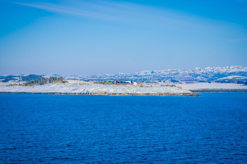 Outdoor view of wooden houses a long in the coast from Hurtigruten voyage cruise ship, Northern Norway. In a gorgeous sunny day and blue sky royalty free stock images