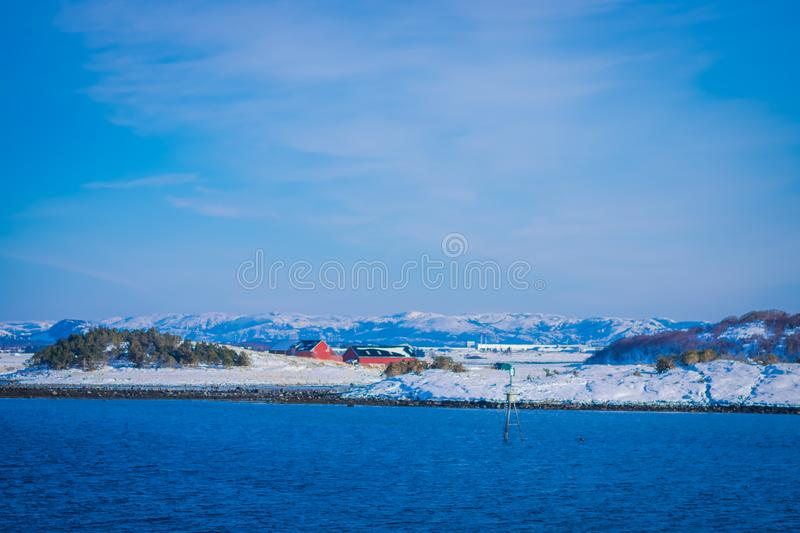 Outdoor view of wooden houses a long in the coast from Hurtigruten voyage cruise ship, Northern Norway. In a gorgeous sunny day and blue sky stock photo
