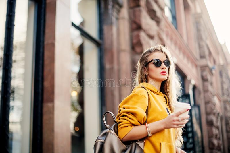 Outdoor waist up portrait of young beautiful woman with long hair. Model wearing stylish sunglasses, clothes, holding bag. City li stock images
