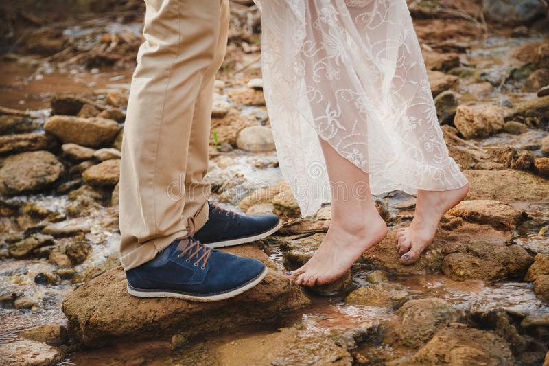 Outdoor wedding ceremony, close up of young woman feet standing barefoot on stones in front of mans feet wearing dark blue shoes stock photos