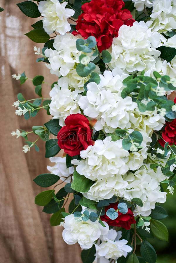 Outdoor wedding decorations, fragment of arch decorated with red and white flowers royalty free stock photography