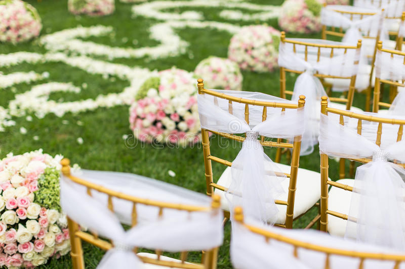 Outdoor wedding Scene. Chairs and flowers at an outdoor wedding royalty free stock images