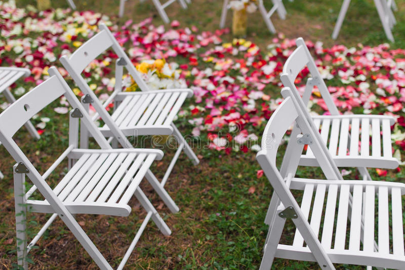Outdoor wedding Scene. Chairs and flowers at an outdoor wedding royalty free stock photos