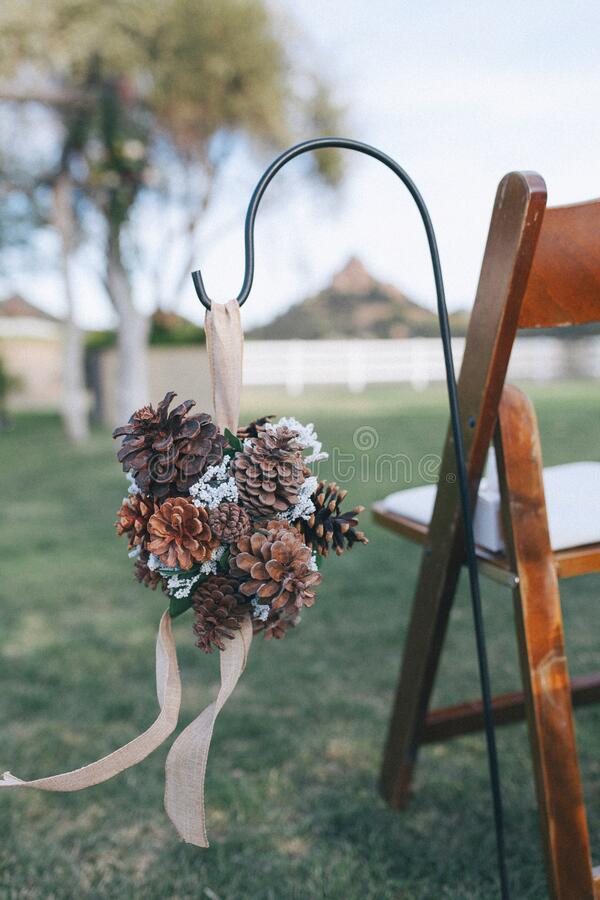 Outdoor winery wedding venue, pine cones decor details. Outdoor wedding venue with brown chairs, vintage wine barrels and beautiful flower arrangements with royalty free stock photo