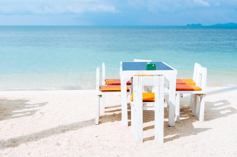 Outdoor white dinner table setting on white sand summer beach an stock photo