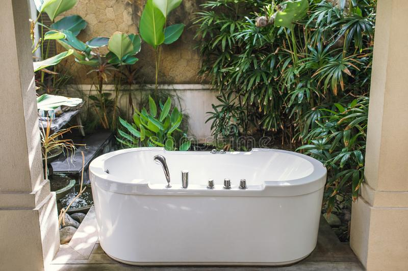 Outdoor white stone bath on tropical background. Outdoor white stone empty bath over green tropical nature background. Spa relaxation concept royalty free stock image