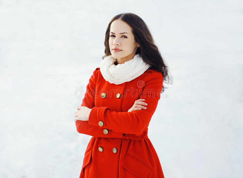 Outdoor winter portrait of beautiful woman. Dressed a red jacket in snowy day stock images