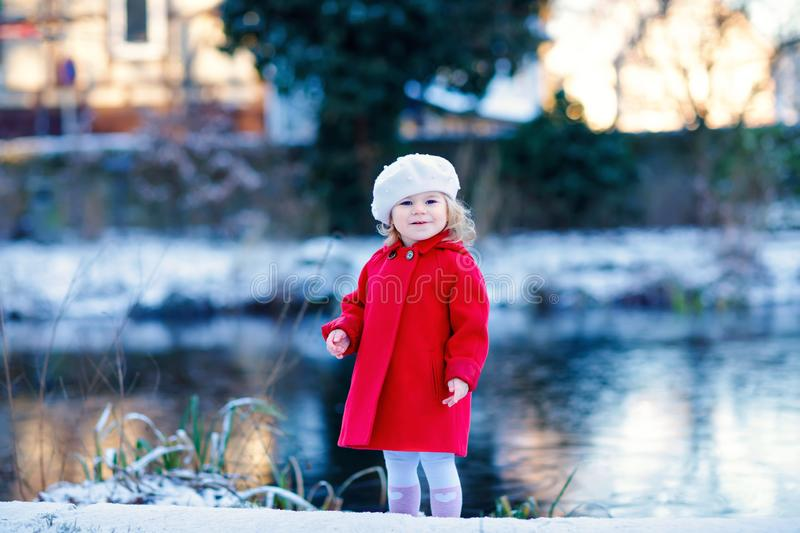 Outdoor winter portrait of little cute toddler girl in red coat and white fashion hat barret. Healthy happy baby child stock photo
