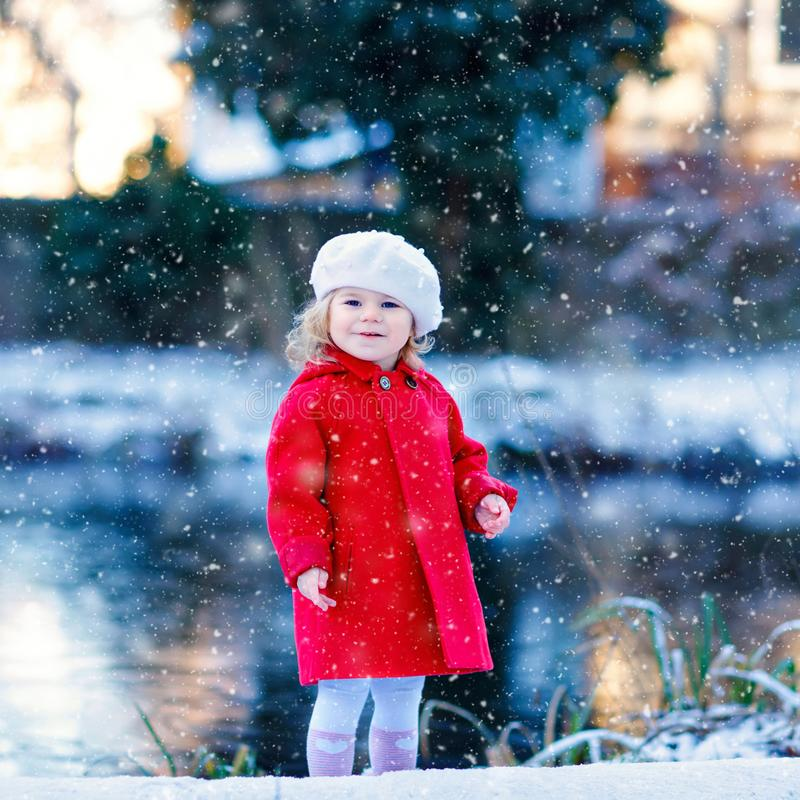 Outdoor winter portrait of little cute toddler girl in red coat and white fashion hat barret. Healthy happy baby child stock images