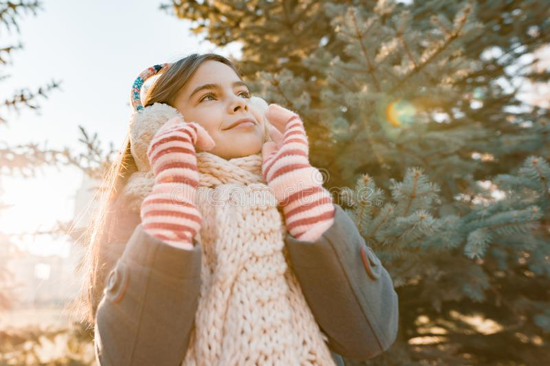 Outdoor winter portrait of a little smiling girl in a knitted scarf near the Christmas tree, golden hour stock photography