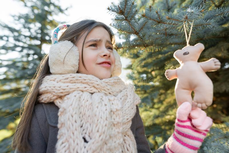 Outdoor winter portrait of smiling girl near Christmas tree stock images