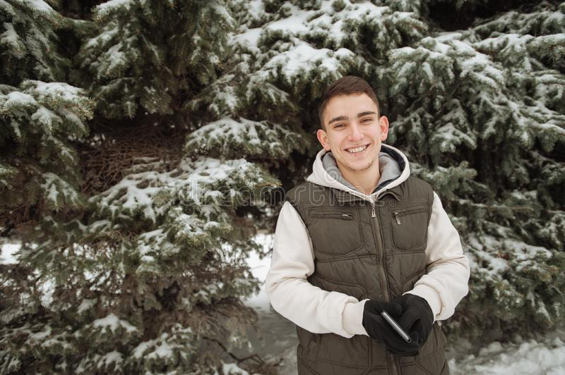 Outdoor winter portrait for young handsome man. Beautiful teenager in his jacket and vest posing on a city street, background of f. Outdoor winter portrait for royalty free stock photos