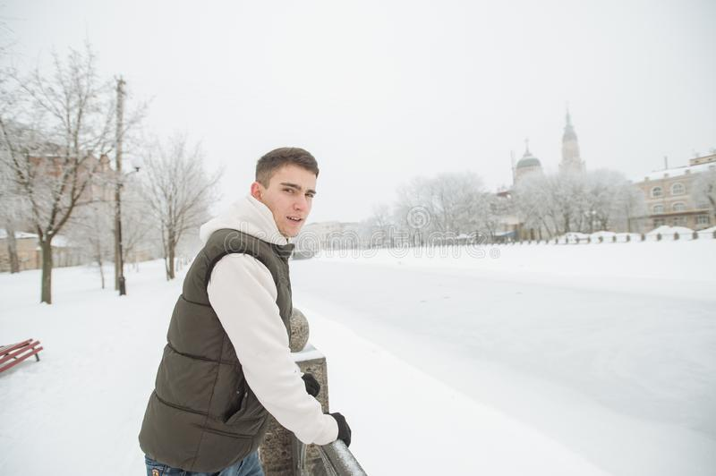 Outdoor winter portrait for young handsome man. Beautiful teenager in his jacket and vest posing on a city street, background of f stock photo