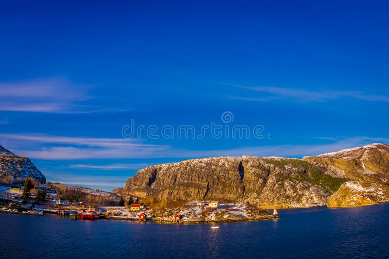 Outdoor winter views of wooden houses a long in the coast from Hurtigruten voyage, Northern Norway. In a gorgeous sunny day and blue sky stock photography