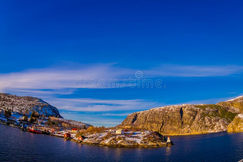 Outdoor winter views of wooden houses a long in the coast from Hurtigruten voyage, Northern Norway. In a gorgeous sunny day and blue sky stock image