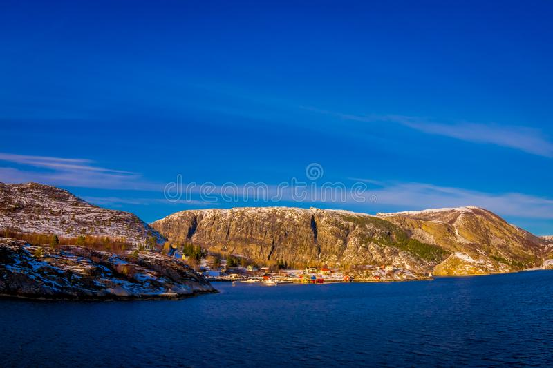 Outdoor winter views of wooden houses a long in the coast from Hurtigruten voyage, Northern Norway. In a gorgeous sunny day and blue sky royalty free stock photography