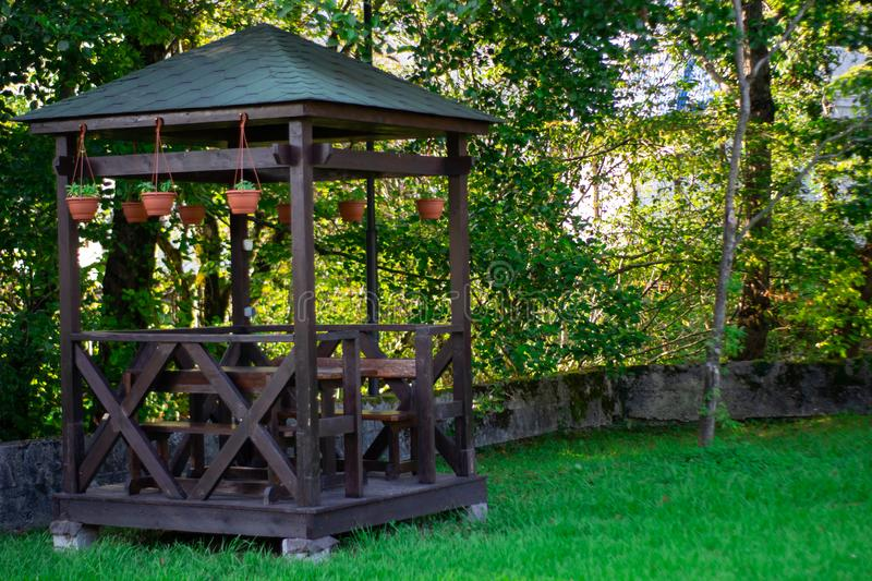 Outdoor wooden gazebo over summer landscape background. Wood brown arbour on green lawn. Summertime lush foliage pine trees blue stock image
