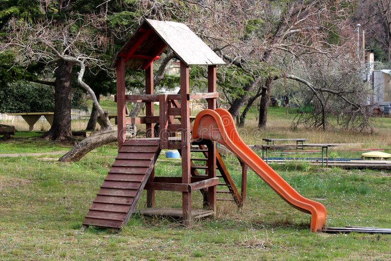 Outdoor wooden public playground equipment with climbing steps and slide. Outdoor wooden public playground equipment with climbing steps and plastic slide stock photo