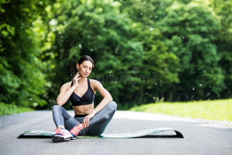 Outdoor workout woman. Fitness woman runner sitting after training outside in park stock images