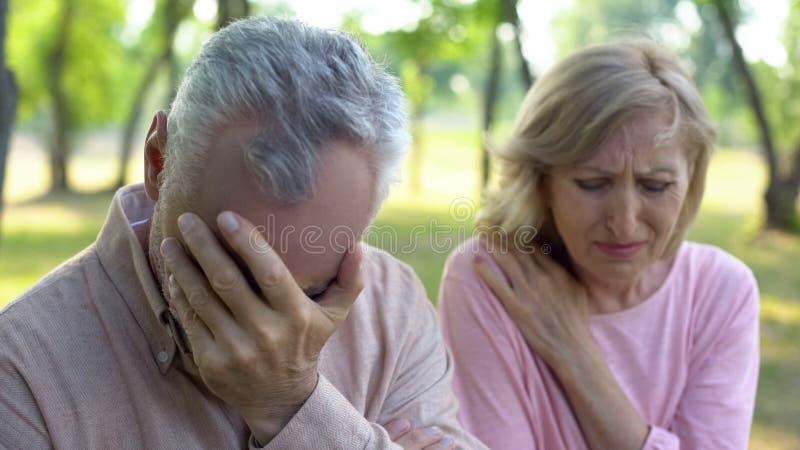 Outdoors зрелых пар плача сидя, неизлечимая болезнь, проблема выхода на пенсию стоковое фото rf
