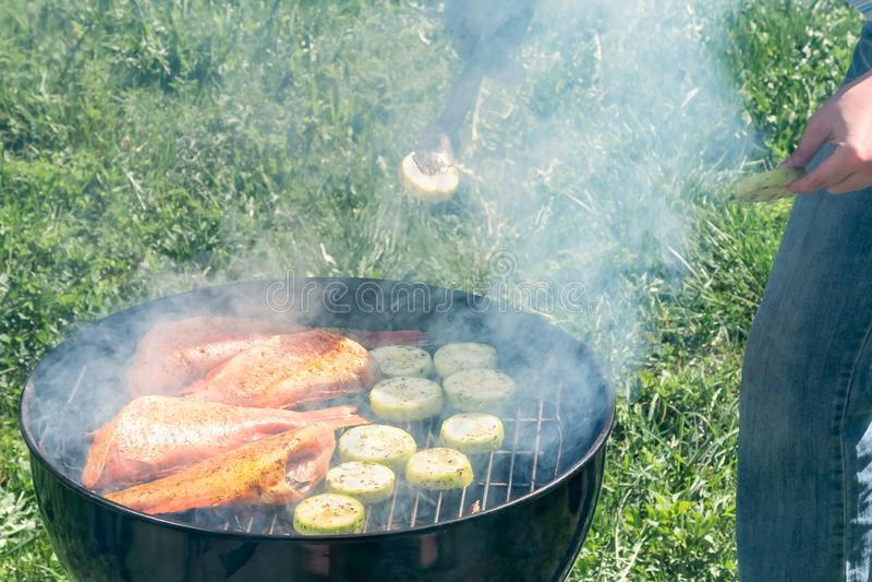 Outdoors пикника летом Варить на круглом морском окуне рыб гриля и кусках цукини стоковое фото rf