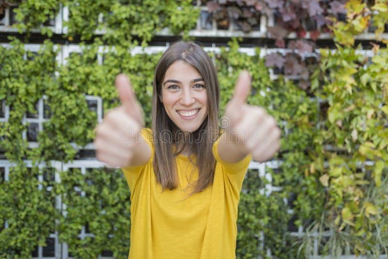 Outdoors портрета красивой молодой женщины с большими пальцами руки вверх и усмехаться Носить желтую случайную рубашку над зелено стоковые фото