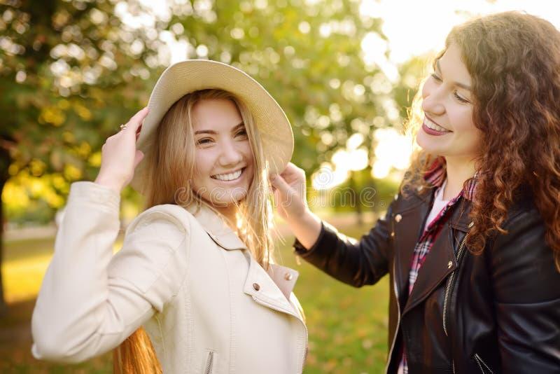 Outdoors портрет веселой молодой женщины 2 Подруга 2 кавказских имея потеху совместно во время прогулки в солнечном парке стоковое фото rf