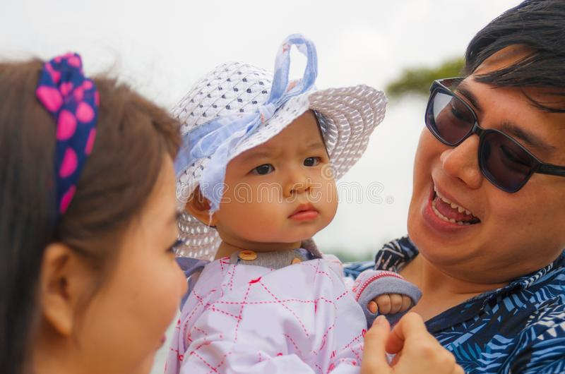 Outdoors candid lifestyle portrait of young happy and proud Asian Chinese couple as loving parents holding adorable daughter baby royalty free stock photo