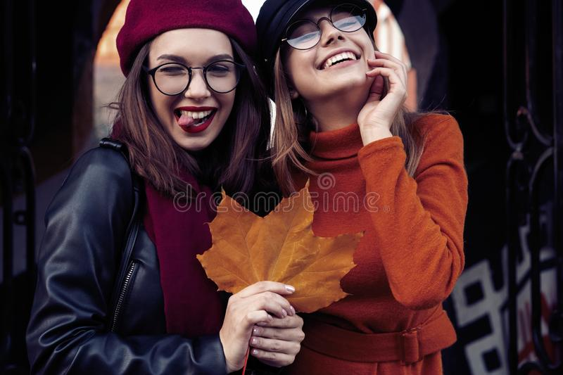 Outdoors fashion portrait young pretty best girls friends in friendly hug. Walking at the city. Posing at the street stock images