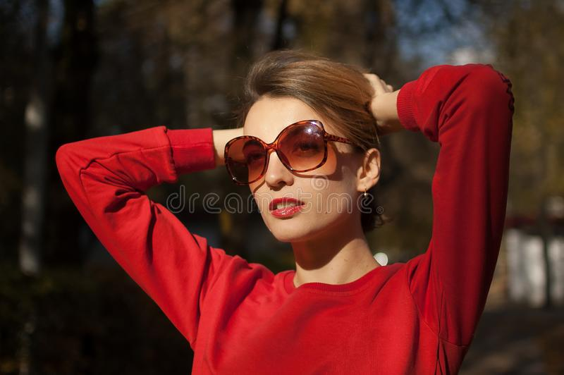 Outdoors female portrait of attractive young woman in fashionable sunglasses with charming smile, blond short hair. Sensual lips, and red clothes posing on the royalty free stock photos