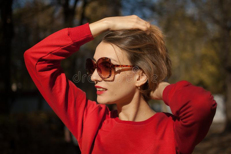 Outdoors female portrait of attractive young woman in fashionable sunglasses with charming smile, blond short hair. Sensual lips, and red clothes posing on the stock image