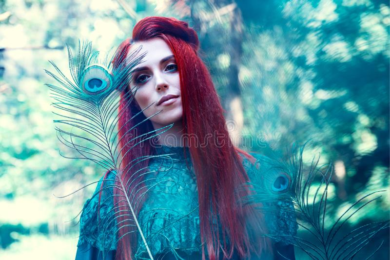 Female portrait with peacock feather on foreground. beauty makeup. stock photo