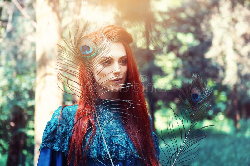 Female portrait with peacock feather on foreground. beauty makeup. royalty free stock photo