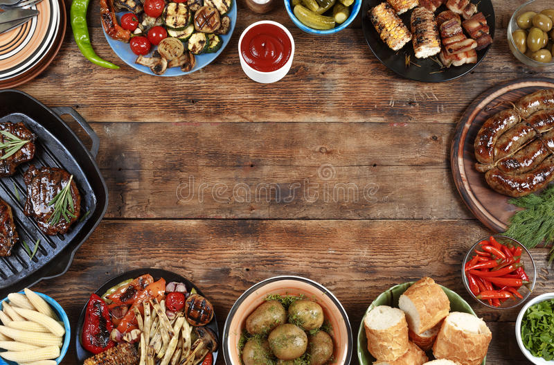 Outdoors Food Concept. Delicious barbecued steak, sausages and grilled vegetables on a wooden picnic table with copy stock image