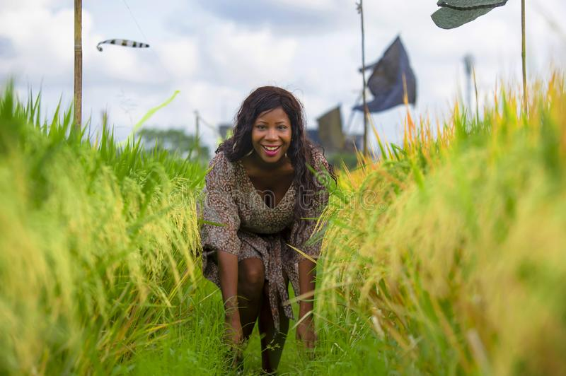 Outdoors fresh portrait of young beautiful and happy black afro American woman in cool dress having fun at tropical rice field stock image