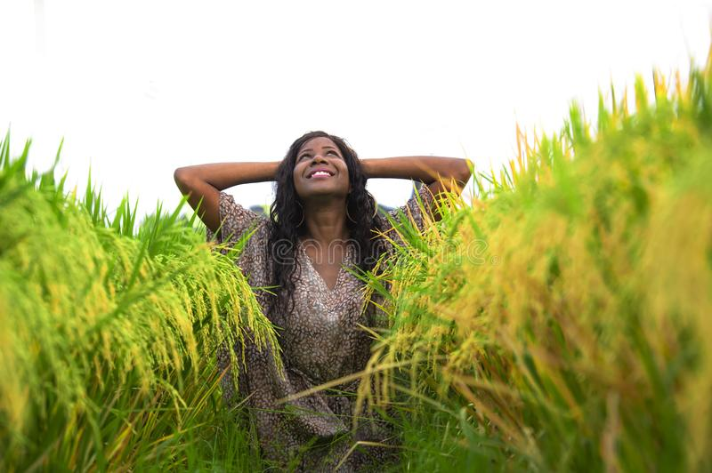 Outdoors fresh portrait of young beautiful and happy black afro American woman in cool dress having fun at tropical rice field. Enjoying exotic holidays trip in stock photos