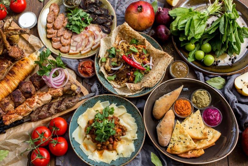 Outdoors karmowy pojęcie Apetyczny barbecued stek, kiełbasy i piec na grillu warzywa na drewnianym pyknicznym stole, zdjęcie royalty free