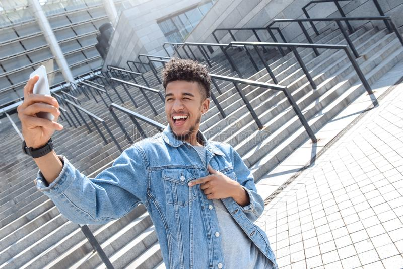 Outdoors Leisure. Mulatto guy standing near stairs taking selfie on smartphone laughing playful royalty free stock images