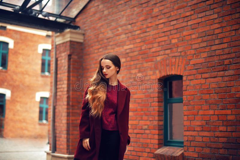 Outdoors lifestyle fashion portrait of brunette girl. Wearing stylish red coat. Walking to the city street. Long curly light hair. stock image