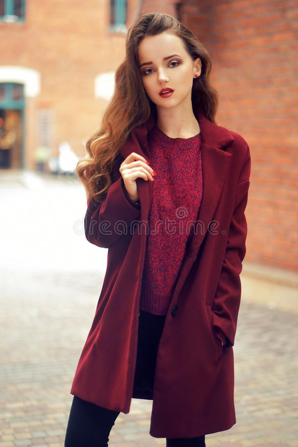 Outdoors lifestyle fashion portrait of brunette girl. Wearing stylish red coat. Walking to the city street. Long curly light hair. stock images