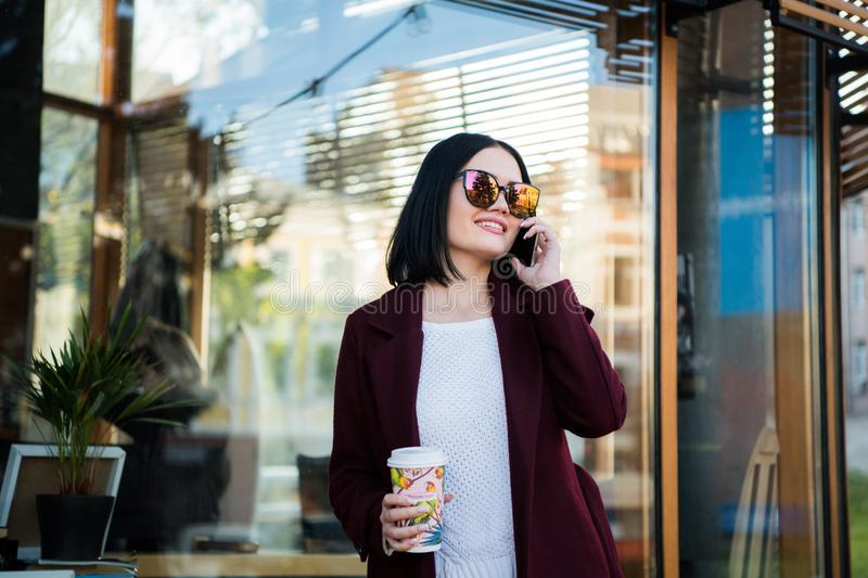 Outdoors lifestyle fashion portrait of pretty young woman talking on the phone. Smiling, walking on the city street royalty free stock image