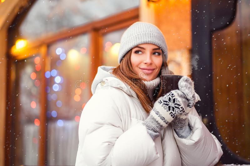 Outdoors lifestyle fashion portrait of stunning girl walking on the holiday city. Smiling, drinking coffee and enjoying royalty free stock photos
