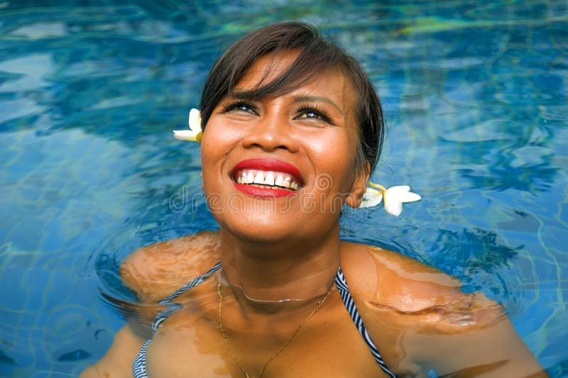 Outdoors lifestyle portrait of middle aged 40s or 50s attractive and happy Asian Indonesian woman in biking enjoying holidays at. Bali villa or tropical resort royalty free stock image