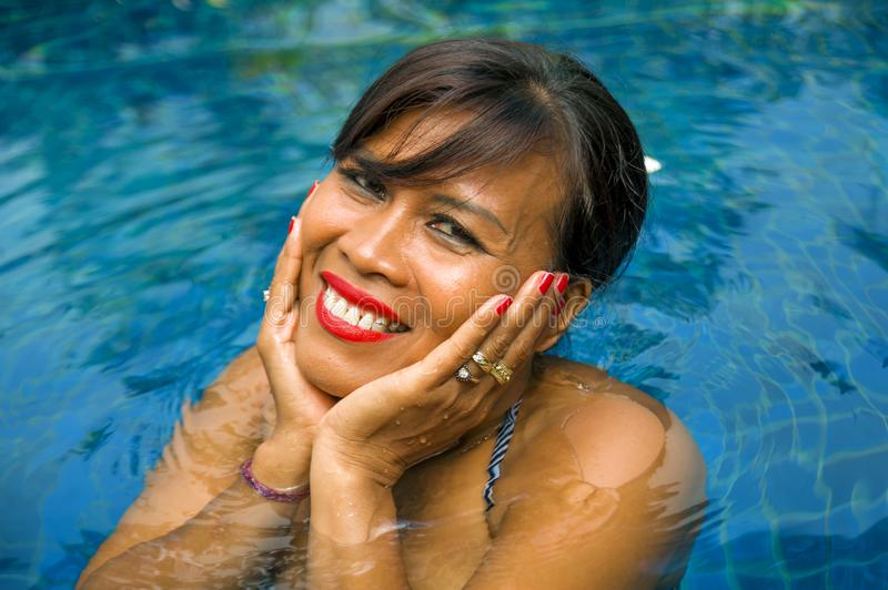 Outdoors lifestyle portrait of middle aged 40s or 50s attractive and happy Asian Indonesian woman in biking enjoying holidays at. Bali villa or tropical resort royalty free stock photos