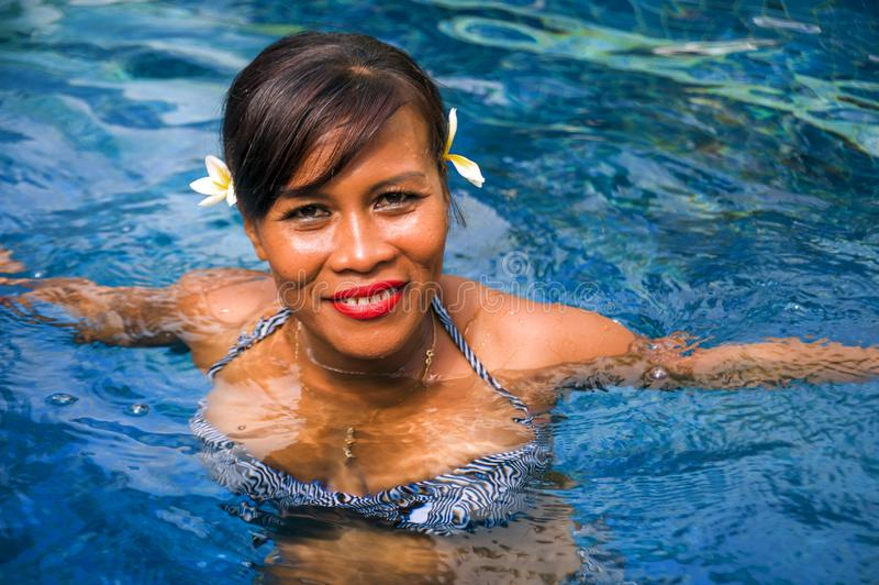 Outdoors lifestyle portrait of middle aged 40s or 50s attractive and happy Asian Indonesian woman in biking enjoying holidays at. Bali villa or tropical resort royalty free stock photo